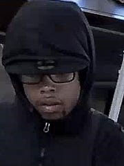 "The suspect is described as a black male, approximately 25 years old, 5'07"" to 5'10"" tall, slim build, slight acne scarring on cheeks, wearing a black hooded jacket."