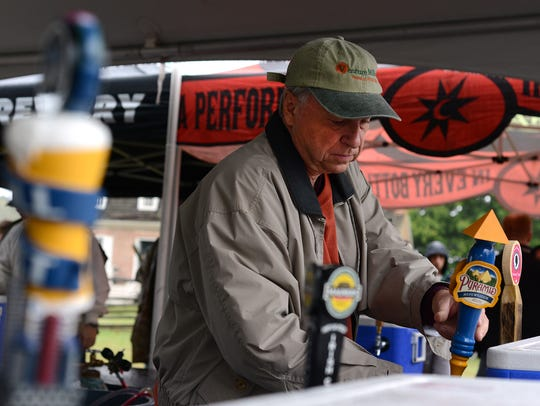 Jack Alexander of Salisbury pours samples of beer at