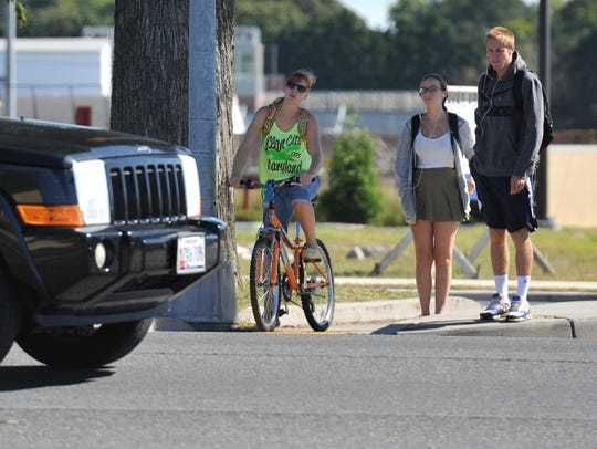 College students wait to cross Route 13 at Dogwood