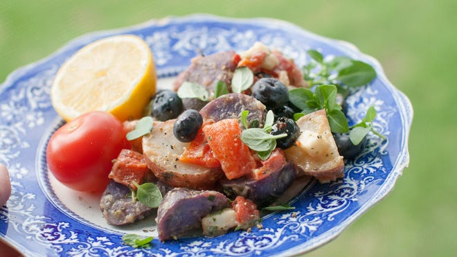 Red and purple potatoes, roasted red peppers, cubes of white goat cheese, and several cups of blueberries provide patriotic colors that reflect the spirit of the Fourth of July holiday in this potato salad recipe.