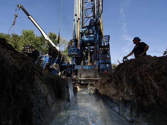 Josh Matthews keeps watch of the machinery as a well is drilled at a home Thursday in Hampton Falls, N.H.