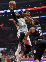 Cleveland Cavaliers forward LeBron James, left, shoots as Los Angeles Clippers guard Sindarius Thornwell defends during the first half of an NBA basketball game Friday, March 9, 2018, in Los Angeles. (AP Photo/Mark J. Terrill)