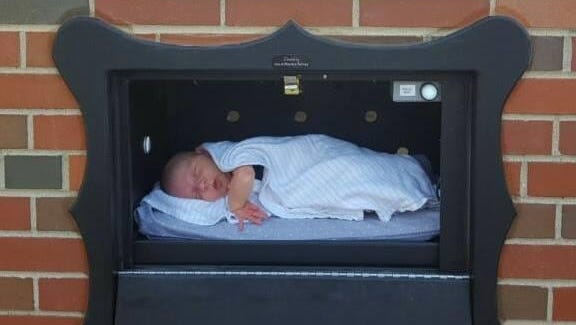 "An infant rests inside a ""baby box"" installed in Indiana in a photo posted to the Safe Haven Baby Boxes Facebook page in November."