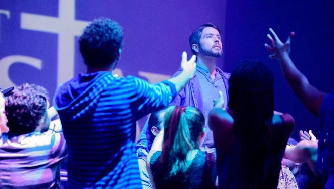 "Jesus (Jonathan Rigsby) receives the devotion of his disciples in ""Jesus Christ Superstar."""