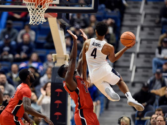 Connecticut's Jalen Adams goes up for a basket and is fouled by Stony Brook's Tyrell Sturdivant, center, as Stony Brook's Junior Saintel, left, looks on, during the second half of an NCAA college basketball game, Tuesday, Nov. 14, 2017, in Hartford, Conn. (AP Photo/Jessica Hill)