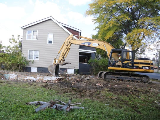 Jason Danneels, an operator engineer, helps pull down houses in the 1500 block of Alter in Detroit Wed., Oct. 7, 2015. A total of ten homes are being taken down erasing eyesores that have plagued the neighborhood for years.