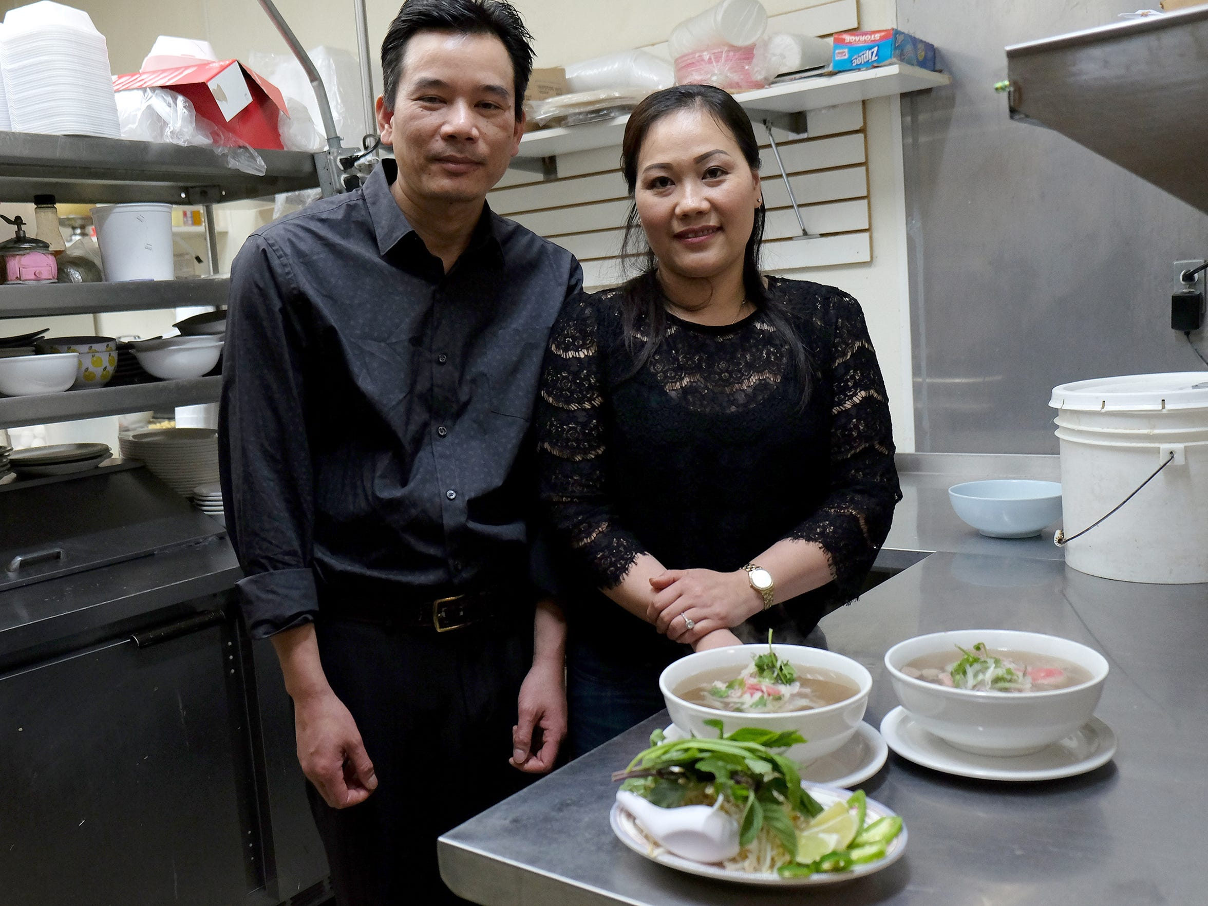Restaurant owners Quyet Phan, left, and Hien Le say their pho -- Vietnamese beef noodle soup, foreground -- is identical to pho served in Vietnam.