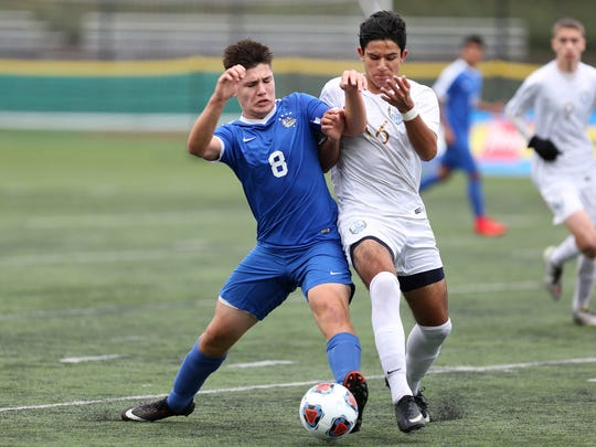 Woodburn's Trevor Karsseboom (8) and Corvallis' Edgar Monroy (16) fight for the ball in the Woodburn vs. Corvallis OSAA Class 5A championship boys soccer match at Hillsboro Stadium on Saturday, Nov. 11, 2017.