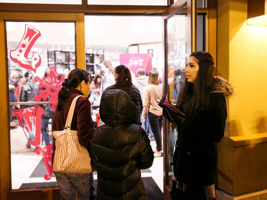 Tanna Coughran lets in 30 shoppers at a time to the Coach store at Woodburn Premium Outlets on Thursday, Nov. 23, 2017. Many stores at the outlet opened at 6 p.m. on the evening of Thanksgiving as shoppers got a jumpstart on holiday shopping.