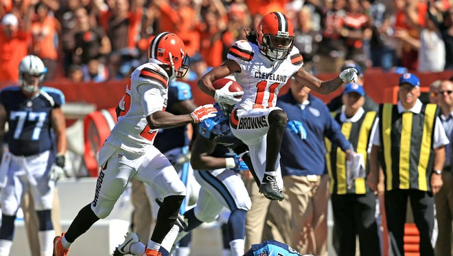 Browns wide receiver Travis Benjamin (11) jumps over Titans punter Brett Kern on a punt return for a touchdown during the second quarter at FirstEnergy Stadium.