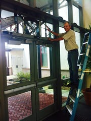 Craig McCullan installs stained glass artwork at the Rosa Parks Transportation Center.