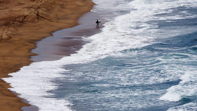 A surfer enters the water Aug. 2 at a beach in Montara, Calif. A cooling pattern in the eastern Pacific ocean may be balancing global warming, a new study suggests.