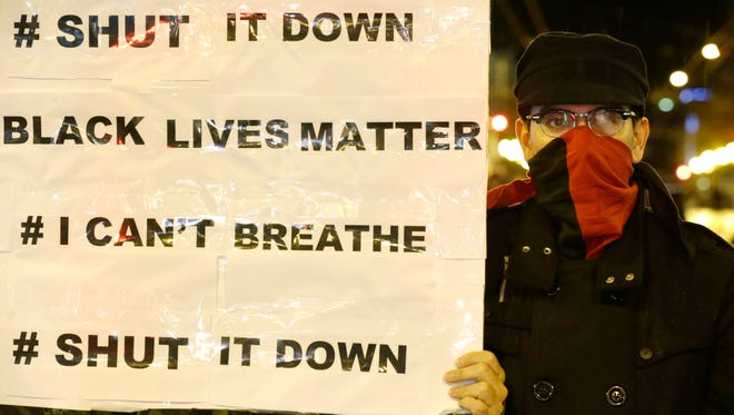 A protester stands next to a sign listing popular hashtags and slogans of the current police protest movement on Dec. 8, 2014, in downtown Seattle during a protest against the decisions not to indict police officers who who killed men in Ferguson, Mo., and New York.