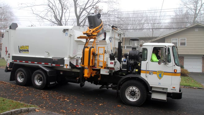 A White Plains sanitation truck with a side loader picks  up garbage on Milford Drive Dec. 5, 2011. Residents have been provided with specially designed garbage cans that the truck is equipped to be able to pick up and set back down.