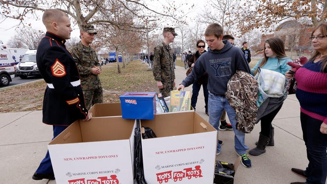 Fans donate toys to the Toys for Tots program outside LP Field before an NFL football game between the Tennessee Titans and the New York Jets Sunday, Dec. 14, 2014, in Nashville, Tenn. (AP Photo/James Kenney)