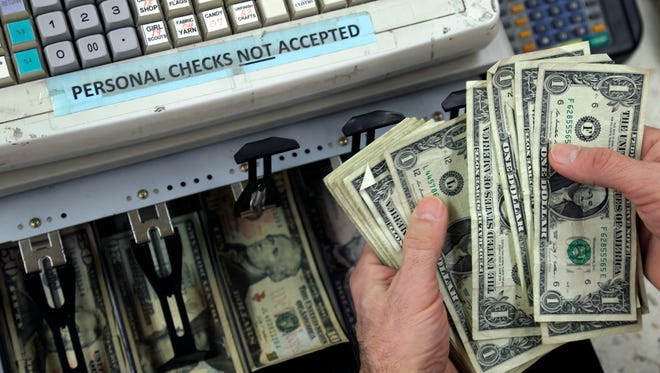 In this Monday, Feb. 25, 2013 photo, a clerk poses for a photo showing cash in the register at Vidler's 5 & 10 store in East Aurora, N.Y.