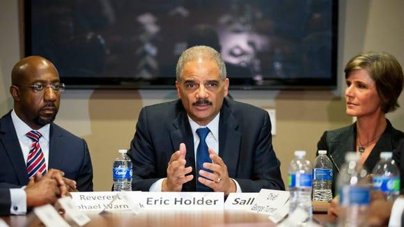 U.S. Attorney General Eric Holder, center, sits next
