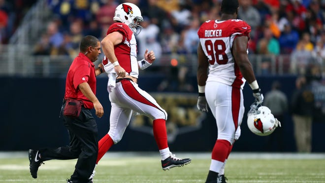 Drew Stanton of the Arizona Cardinals hobbles off the field after being sacked by Aaron Donald of the St. Louis Rams in the third quarter on Dec. 11, 2014 in St Louis.