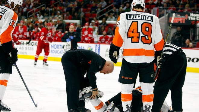 Philadelphia Flyers trainer looks at Philadelphia Flyers forward Claude Giroux (28) leg during the third period against the Carolina Hurricanes at PNC Arena.