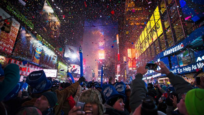 Revelers cheer under falling confetti at the stroke of midnight during the New Year's Eve celebration in Times Square.