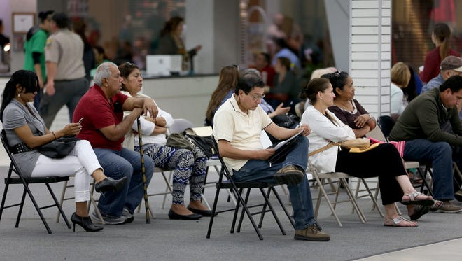 People wait to sign up for health insurance in Miami.