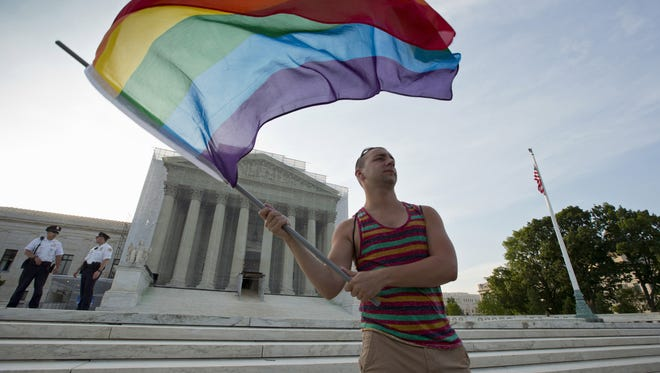 Gay rights advocate Vin Testa waves a rainbow flag in front of the Supreme Court in Washington.
