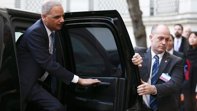 U.S Attorney General Eric Holder, left, steps out a car before the start of an international meeting aimed at fighting terrorism, in Paris, France, Sunday, Jan. 11, 2015.