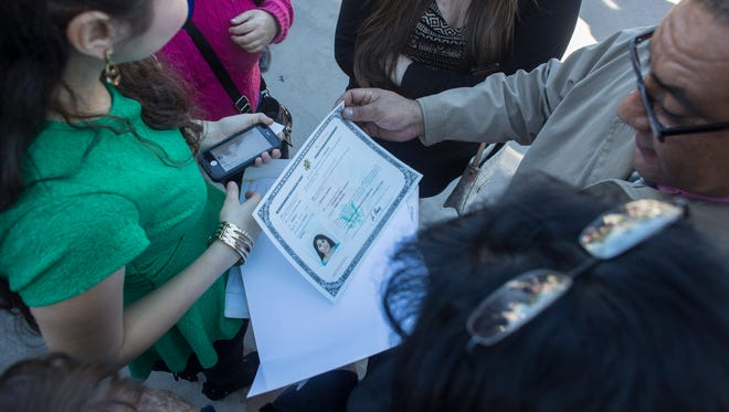 Family of Filomena Parra, from Durango, Mexico, look over her Certificate of Naturalization during Chandler Citizenship Naturalization Ceremony at the Chandler Public Library in Chandler, AZ on January 17, 2015.