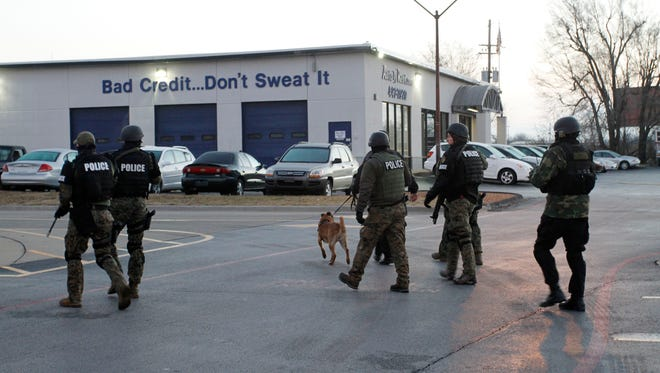 Police search in the parking lot of Rent to Own Autos at Glenstone Ave. and Chestnut Exp., near where a police officer was shot on Monday, January 26, 2015.