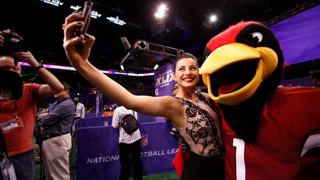 ESPN international reporter Karina Correa takes a selfie with the Arizona Cardinals mascot during media day for Super Bowl XLIX at US Airways Center in Phoenix on Jan. 27.