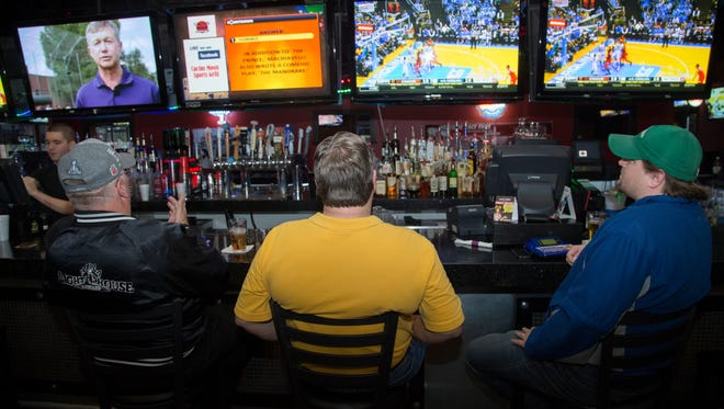 Hayden Lancaster, left, Pete Phillips and Brent Dunford, right, answer some trivia questions as they hang out at Cactus Moon Sports Grill in Mesa, Ariz., on Jan. 26, 2015. The group of locals have been coming to the bar for the past four years.