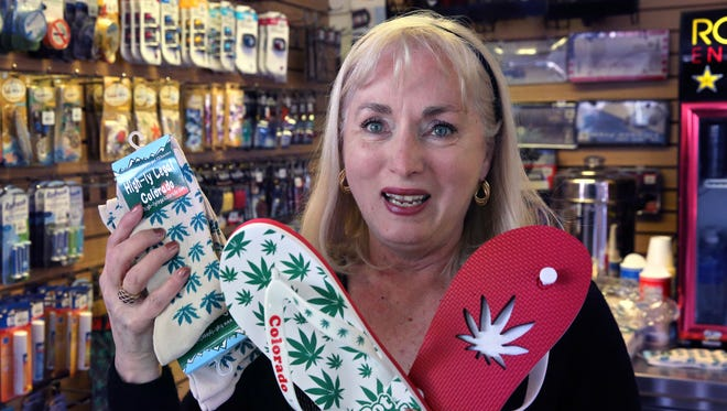 """In this Jan. 27, 2015 photo, former school teacher and current souvenir entrepreneur Ann Jordan displays a few of her products, socks and flip-flops decorated with marijuana-themes, as she drops off supplies to one of her sellers, the Red Carpet Car Wash and Detailing, in Aurora, Colo. Marijuana is legal in Colorado, but not at its largest airport - and now Denver International Airport wants to keep out weed-themed souvenirs, too. A policy enacted this month bans the sale of souvenirs depicting marijuana leaves or Colorado's ubiquitous """"Mile High"""" pot puns."""