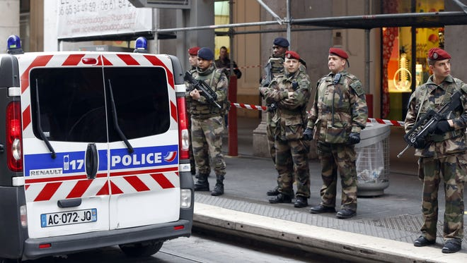 Soldiers stand guard next to a police van outside the Jewish Community Center where three soldiers were attacked by a man with a bladed weapon, on Feb. 3, 2015 in downtown Nice, southeastern France.