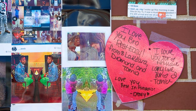 Photos and messages for A.I. duPont freshman Jordon Ellerbe, 16, hang in front of his home on Rodney Street in the days after his death.