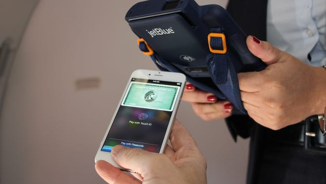 Using TouchID to verify a purchase on a JetBlue flight using Apple Pay.