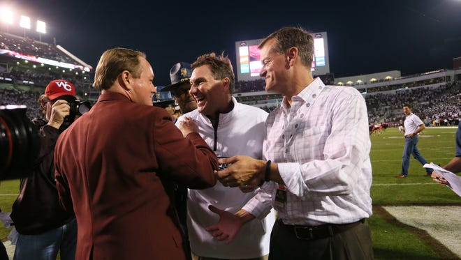 Mississippi State president Mark E. Keenum (left) and athletic director Scott Stricklin congratulate head coach Dan Mullen. Mississippi State played Auburn in a college football game on Saturday, October 11, 2014 at Davis Wade Stadium in Starkville, Miss. (Photo by Keith Warren)