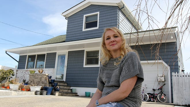 Lisa Vanderveer, a Brick homeowner who wound up suing her flood insurer after they offered her only $35,000 for her Sandy-damaged home and wound up settling for about $110,000, sits outside of her home Friday March 13, 2015. Her house has foundation issues and must be knocked down and elevated.