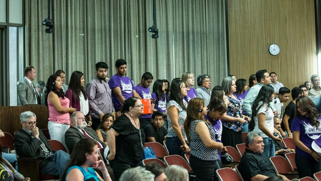 DREAMers stands up during the City Council meeting isten to exploring its options for creating a single municipal ID card for residents to use city libraries, recreation centers and public transit on April 22, 2015.