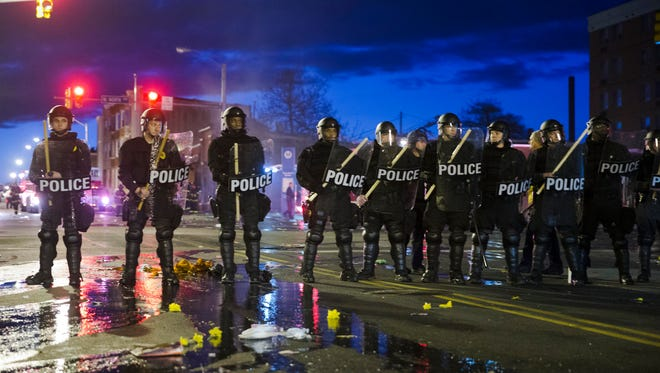 Police stand guard Monday, April 27, 2015, after rioters plunged part of Baltimore into chaos, torching a pharmacy, setting police cars ablaze and throwing bricks at officers.  (AP Photo/Matt Rourke)