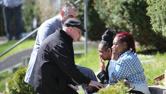 Investigators try to comfort two women who knew the victim of a Post Avenue homicide.