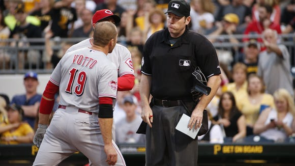 The Reds' Joey Votto (19) is restrained from umpire Chris Conroy, left, by Reds manager Bryan Price, center, after Votto bumped Conroy during an altercation during the third inning of a baseball game against the Pittsburgh Pirates in Pittsburgh on Wednesday. Votto was ejected from the game.