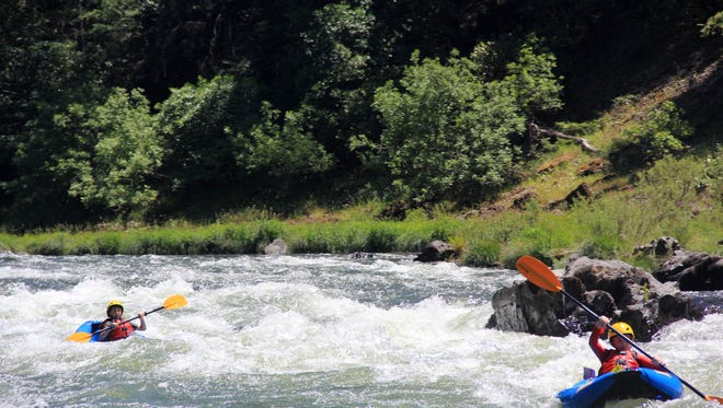Eli and Rylan take inflatable kayaks down the Rogue River.