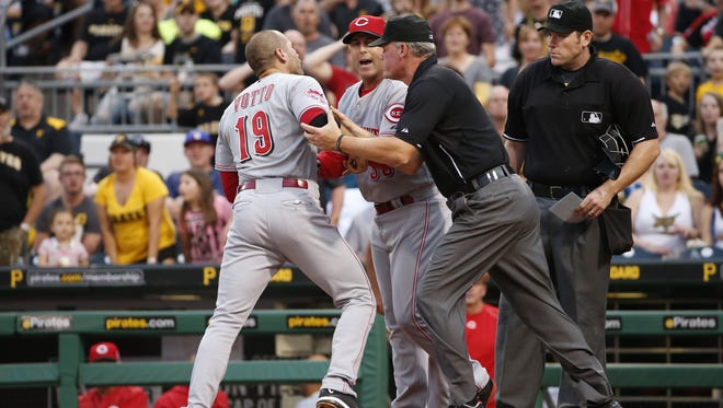 The Reds' Joey Votto (19) is restrained from umpire Chris Conroy, right, by Reds manager Bryan Price, second from left, and umpire Ted Barrett, center, after Votto bumped Conroy during an altercation during the third inning Wednesday in Pittsburgh. Votto was ejected from the game.