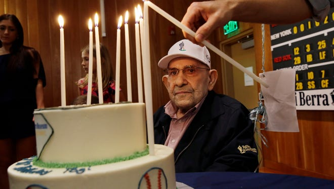 Baseball Hall of Famer Yogi Berra looks on as a candle on his birthday cake is lit.