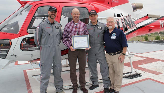 Duane Rorie, the chief flight nurse at Air Link at Medical Center of the Rockies, was honored Monday, May 4, 2015, with the Patriot Award. From left to right in the photo is flight nurse David Steiner, Duane Rorie, flight paramedic Kris Schott and retired Navy Cmdr. Brian Hand of the Employer Support for the Guard and Reserves.