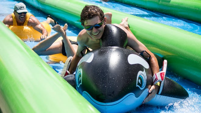 """Participants smile as they splash down """"Slide the City"""" in downtown Phoenix on May 16, 2015. The 1,000-foot traveling vinyl water slide stretched across Seventh Street and hosted nearly 4,500 people."""