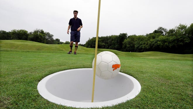 """In a photo from June 20, 2014 in Salem Township, Mich., Brian Eggenberger putts his ball during a round of FootGolf at Fox Hills Golf Course. FootGolf, a soccer-golf hybrid is helping courses draw younger, more diverse customers. Players """"tee off"""" _ minus the tees of course _ by kicking a soccer ball from the tee box. They follow the basic rules of golf from there, advancing the ball until it drops into the oversized hole. (AP Photo/Carlos Osorio)"""