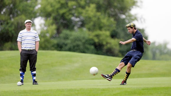 "In a photo from June 20, 2014 in Salem Township, Mich., Josh Maxam, left, watches as Brian Eggenberger drives during a round of FootGolf at Fox Hills Golf Course. FootGolf, a soccer-golf hybrid is helping courses draw younger, more diverse customers. Players ""tee off"" _ minus the tees of course _ by kicking a soccer ball from the tee box. They follow the basic rules of golf from there, advancing the ball until it drops into the oversized hole. (AP Photo/Carlos Osorio)"