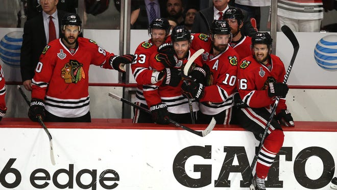 Patrick Kane (No. 88) and former UVM standout Patrick Sharp (No. 10) celebrate with some of their Chicago Blackhawks teammates during Game 6 of the Stanley Cup final.