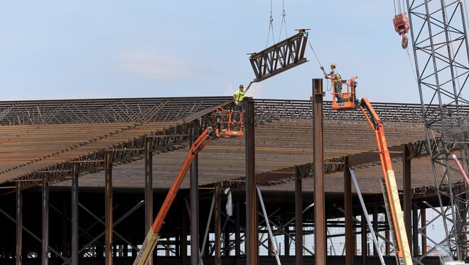 A steel beam is placed as work erecting the frame of the building nears completion. SolarCity has pledged to create 1,460 jobs over the next 10 years, plus 1,400 more in supplier jobs.